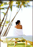 Photo of woman in tropical climate sitting on a massage table looking to sky.
